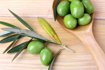 Fototapete - Olive verdi foglie e ramo su un tavolo in legno