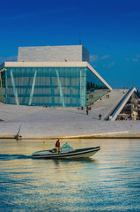 Motorboat floating in front of opera house in Oslo, Norway