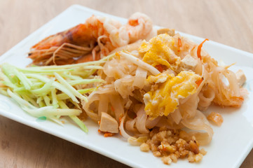 Seafood pad Thai dish of stir fried rice noodles on a square whi