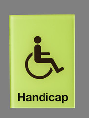 Green glass handicap sign isolated on grey  background