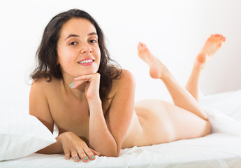 Nude girl on bed at bedroom