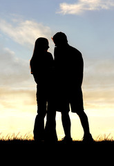 Loving Couple Silhouette Holding Hands at Sunset