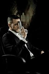 Elegant man sitting in a chair holding  gun over dark background