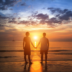 Happy young couple holding hands on sea beach.