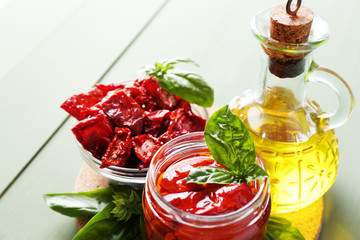 Sun dried tomatoes in glass jar, olive oil in glass bottle,