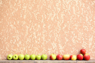 Juicy apples in row on wall background