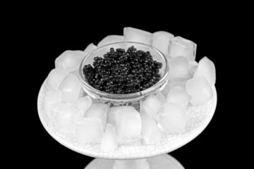 Black caviar in glass bowl and ice in plastic dish
