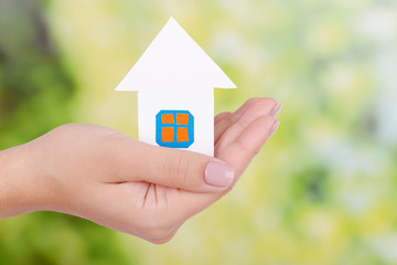 Woman hand holding paper house on bright background