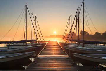 Tranquil, foggy sunrise at a pier with sailing boats.