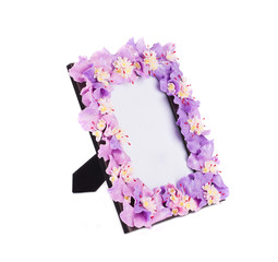 Photo frame with artificial flowers.