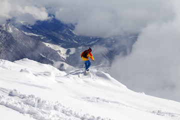 Snowboarder on off-piste slope an mountains in fog