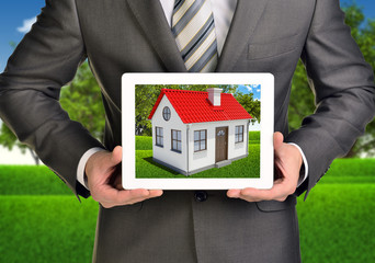 Hands hold tablet pc. Picture of small house with red roof on