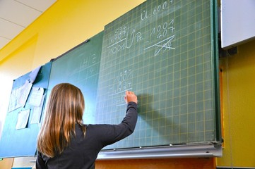 Mädchen schreibt an Schultafel