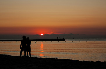 silhouettes of a couple at beach in sunlight