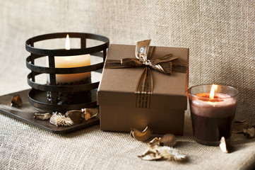 Celebration surprise. Golden-brown gift box with candles
