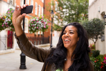 african american woman taking a selfie with her phone.