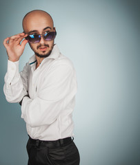 Cute man in sunglasses with beard looking away