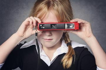 Petite fille rousse avec appareil photo vintage
