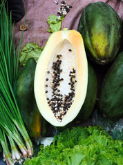 Fresh green half cut papaya on vegetables market of Asia