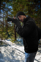 photographer in snowy coniferous forest