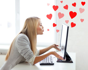 woman sending kisses with computer monitor