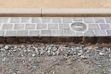 Eine neue Strassenkappe für Wasser montiert im Strassenpflaster