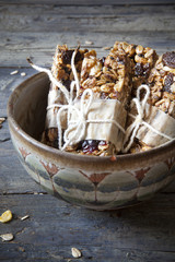homemade rustic granola bars with dried fruits on old bowl