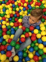 kid having fun at a ball pool