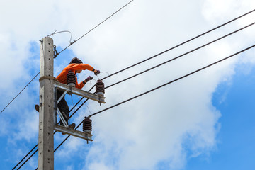 electrician working  repairing wire on electric power pole