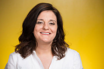 Headshot smiling middle aged woman on yellow background