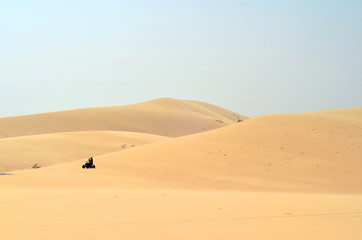 People chasing around sand dunes on a quad bike