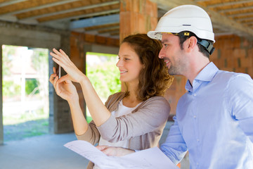 Young woman and architect on construction site