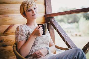 Woman sitting in a wicker chair on a balcony with a cup of tea