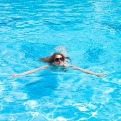 Молодая девушка в очках плавает в бассейне
