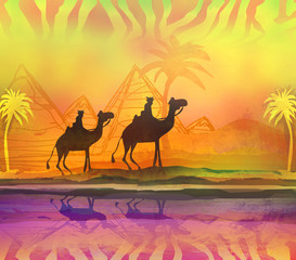 Camel train silhouetted against colorful sky crossing the Sahara