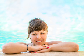Portrait of a cheerful and beautiful girl in the pool water