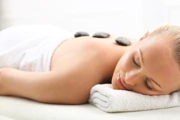 Obraz Masaż gorącymi kamieniami, kobieta w salonie spa - fototapety do salonu
