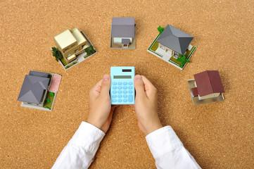 コルクボードの上に扇形に並んだ住宅模型と電卓