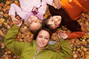Woman with kids on the autumn ground