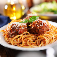spaghetti and meatballs at cluttered dinner table