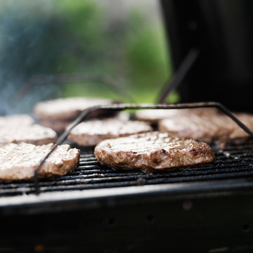 hamubrger patties on a charcoal grill