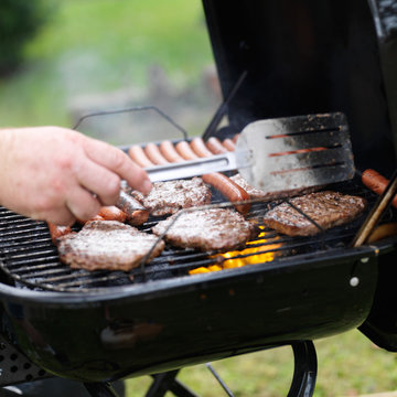 turning food on grill with haumbers and hotdogs