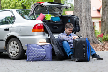 Powerless father next to car trunk