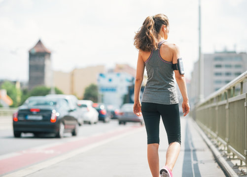 Fitness young woman walking in the city. rear view