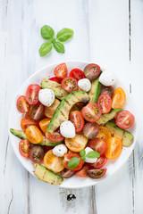 Salad with grilled avocado, tomatoes, mozzarella balls and basil