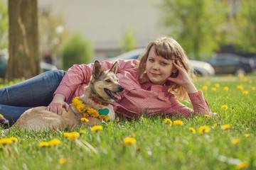 Woman with dog lying on the green grass