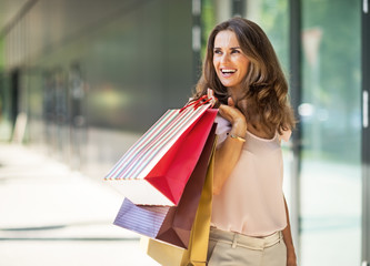 Happy young woman with shopping bags on the mall alley
