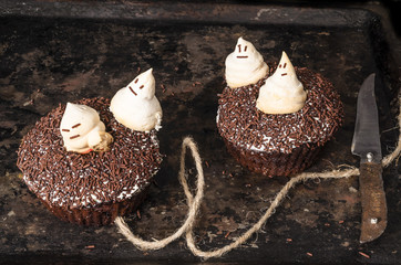 Two chocolate pumpkin cupcakes, decorated with ghosts