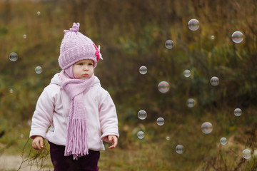 cute little girl at park catching bubbles in autumn
