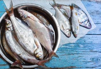 fresh fish in  iron bowl on a wooden background